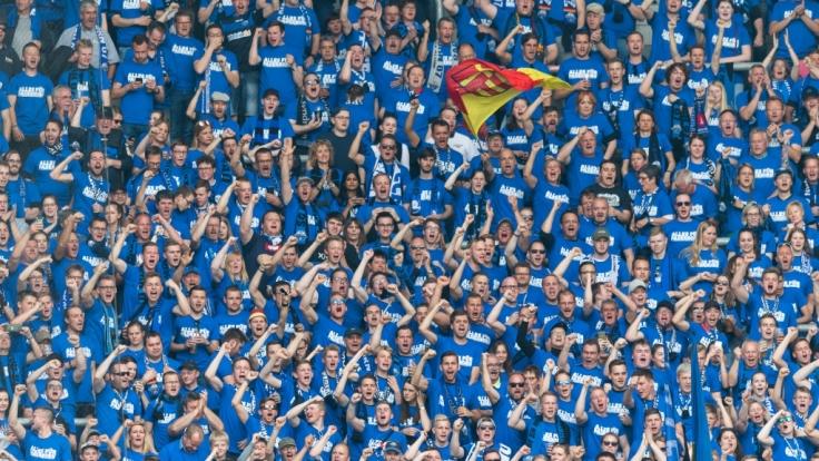 Mit blauen Shirts zeigen die Fans auf der Tribüne ihre Unterstützung für den SC Paderborn. (Symbolbild) (Foto)