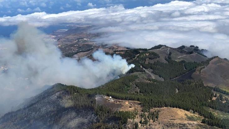 Rauch steigt über die Berge von Gran Canaria auf. Der seit dem Wochenende wütende Waldbrand ist noch nicht unter Kontrolle.