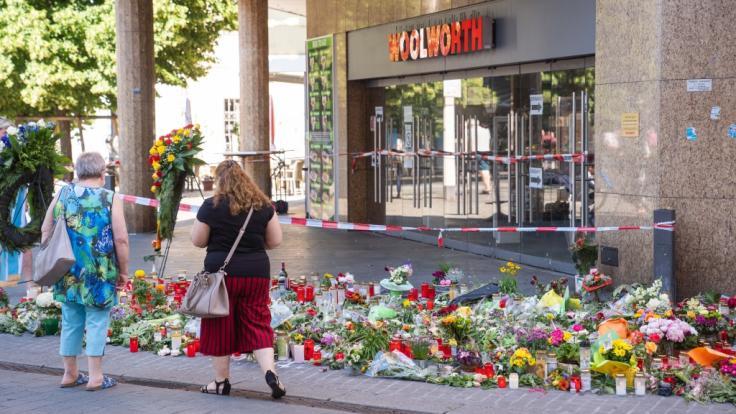 Trauerkerzen und Blumen liegen vor einem Kaufhaus in der Würzburger Innenstadt, in dem ein Mann Menschen mit einem Messer attackiert hatte. (Foto)