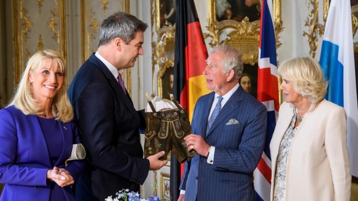 Markus Söder (CSU, l), Ministerpräsident von Bayern, überreicht Prinz Charles einetraditionelle Lederhose für das neugeborene Baby Archie Harrison von Herzogin Meghan und Prinz Harry. (Foto)