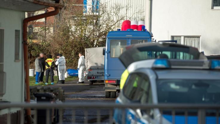 Polizisten stehen auf dem umzäunten Grundstück. Dort hatten Nachbarn das tote Rentner-Ehepaar gefunden. (Foto)
