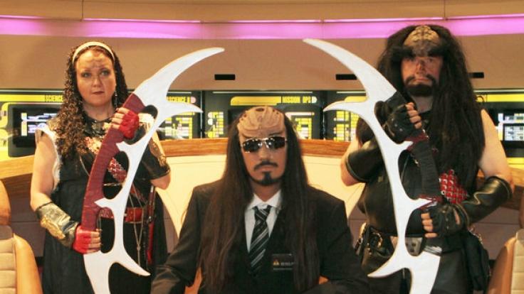Der Sprachexperte für Klingonisch, Lieven L. Litaer (Mitte), und zwei Klingonen-Krieger mit Schwertern befinden sich in der Raumschiffkulisse im Filmpark Babelsberg in Potsdam. Bis zum 31. Oktober 2011 läuft die Ausstellung Star Trek im Filmpark. (Foto)