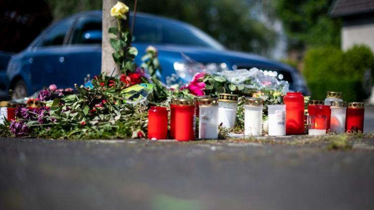 Blumen und Kerzen stehen an der Stelle in Moers, an der eine unbeteiligte Frau bei einem mutmaßlichen illegalen Autorennen verletzt und später gestorben ist.