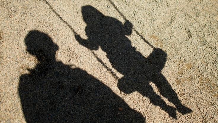 Kindermissbrauch: Schatten von einem Mann und einem Kind auf der Schaukel.