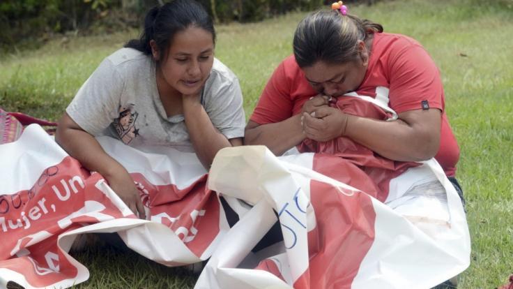 Verwandte der Bürgermeisterkandidatin Karina Garcia, die in der Nacht tot aufgefunden wurde, halten ihr politisches Banner und weinen.