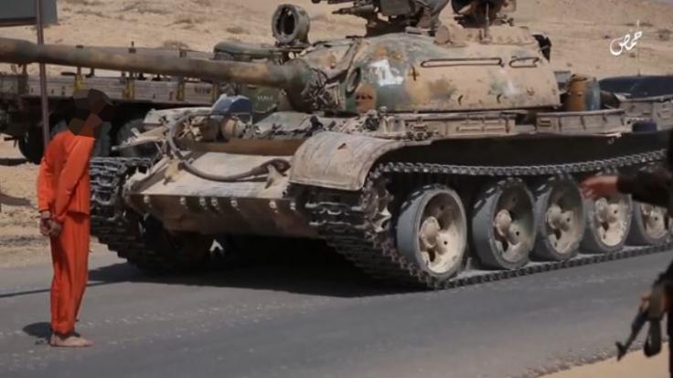 IS-Terroristen überrollen einen Gefangenen mit einem Panzer.