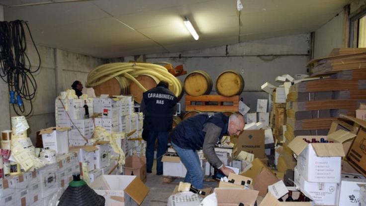 Polizisten durchsuchen in der Nähe von Florenz (Italien) ein Lager, in dem gefälschter Rotwein entdeckt wurde.