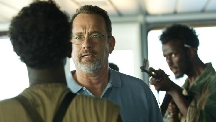 Captain Richard Phillips (Tom Hanks) wird von den Piraten Muse (Barkhad Abdi, l.) und Elmi (Mahat M. Ali, r.) bedroht. (Foto)