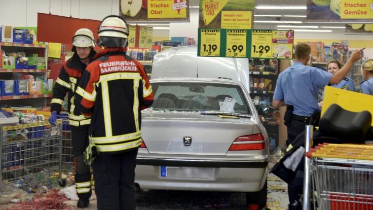 Feuerwehrleute und Polizeibeamte stehen in einem Supermarkt neben einem Pkw, der zuvor in den Supermarkt gefahren war und dabei fünf Menschen verletzt hat.