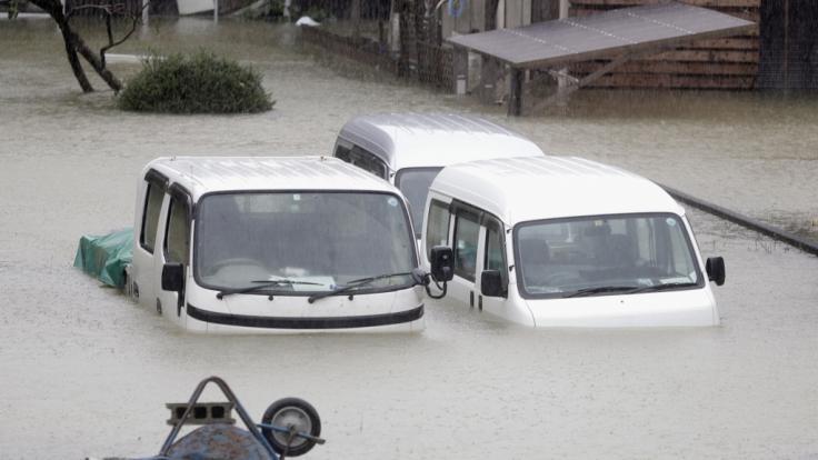 Fahrzeuge stehen in einem überfluteten Wohngebiet der Präfektur Mie. (Foto)