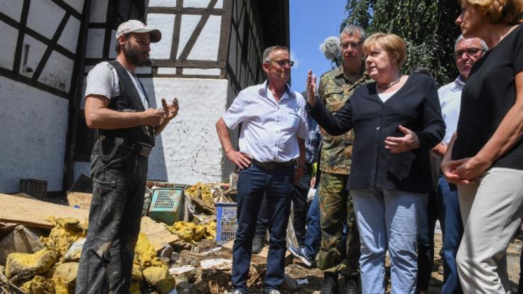 Bundeskanzlerin Angela Merkel (3.v.r.) und Malu Dreyer (r,SPD), Ministerpräsidentin von Rheinland-Pfalz, sprechen mit einem betroffenen Anwohner während ihres Besuchs in dem vom Hochwasser verwüsteten Dorf Schuld bei Bad Neuenahr-Ahrweiler. (Foto)