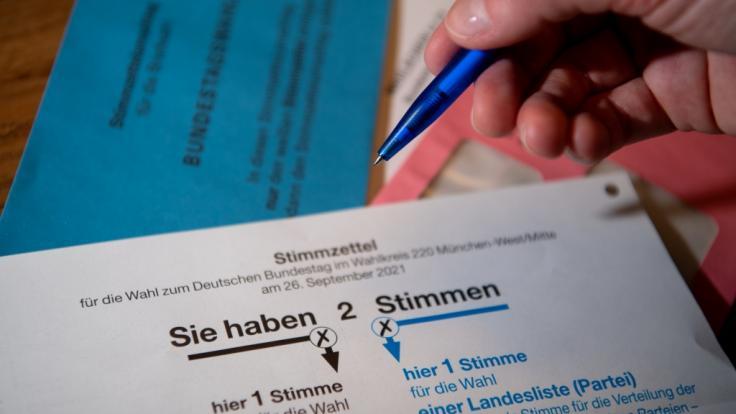 Briefwahlunterlagen für die Bundestagswahl 2021 mit Stimmzettel und Stimmzettelumschlag liegen auf einem Tisch. (Foto)
