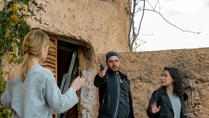 Erik Fritsche (Patrick Heinrich, links), der Ehemann von Shirin (Gamze Senol, rechts), bedroht Sophie (Lea Marlen Woitack, links vorn) mit einer Waffe.