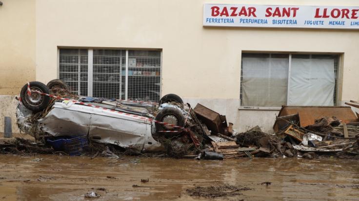Ein Auto liegt nach einem schweren Unwetter auf Mallorca umgedreht auf einer Straße.