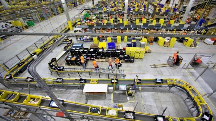 Blick aufs Parkett: Mitarbeiter im Amazon-Standort Leipzig beim Waren-Sortieren. (Foto)