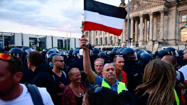 Berlin: Teilnehmer einer Kundgebung gegen die Corona-Maßnahmen stehen vor dem Reichstag.