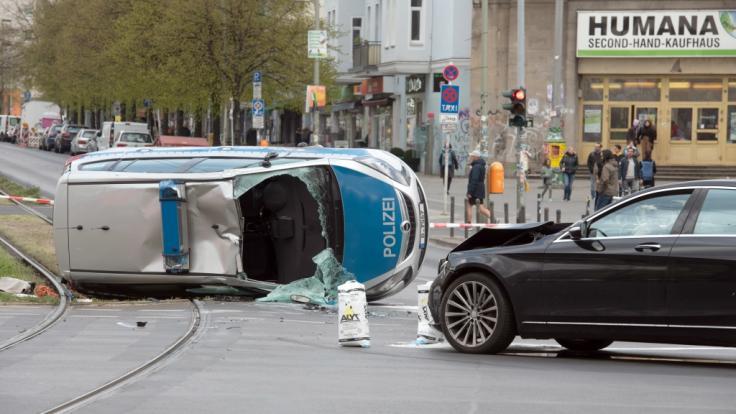 Der umgekippte Streifenwagen liegt nach einem Zusammenstoß mit einem Pkw auf einem Grünstreifen am Frankfurter Tor.