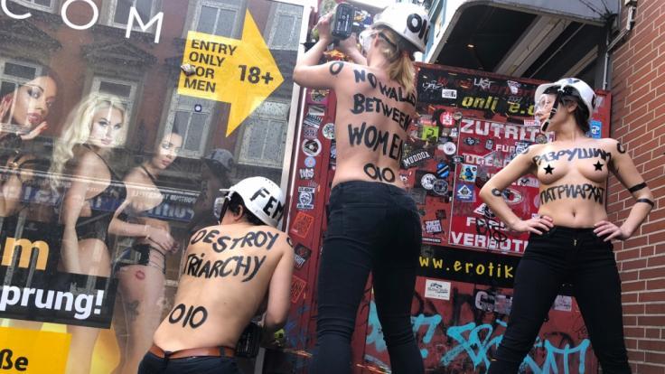 Femen-Aktivistinnen reißen einen Sichtschutz in Hamburgs Rotlichtviertel ein.