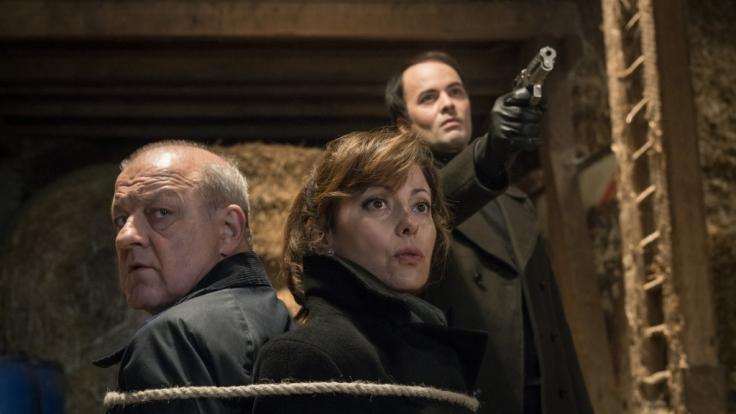 Georg Wilsberg (Leonard Lansink) und Franziska Rudolph (Carolina Vera) sind in einem Kellerraum aneinander gefesselt. (Foto)