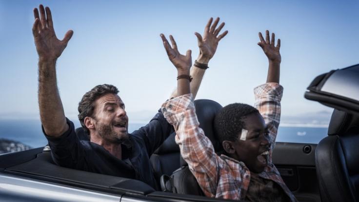 Richard (Stephan Luca, l.) zeigt Keagan (Likho Mango, r.), wie man Auto fährt.