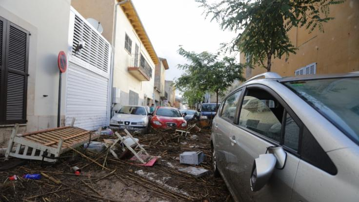 Sant Llorenç des Cardassar: Trümmer und Autos stehen auf einer von Starkregen verwüsteten Straße.
