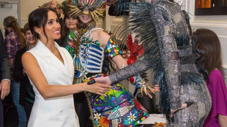 Herzogin Meghan wird von kostümierten Darstellern während ihres Besuchs in der Courtenay Creative im neuseeländischen Wellington begrüßt.