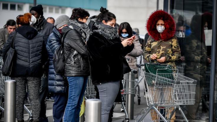In Italien drängen sich Hunderte Menschen vor einem Supermarkt.Nach dem Tod zweier Menschen sind Teile des öffentlichen Lebens in Italien zum Erliegen gekommen.