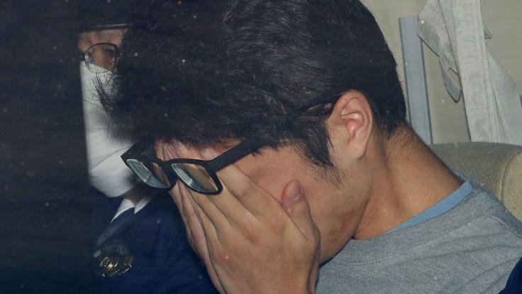 """Der in Japan angeklagte und inzwischen verurteilte """"Twitter-Killer"""" hält seine Hände vors Gesicht, als er aus einer Polizeistation gebracht wird. (Foto)"""