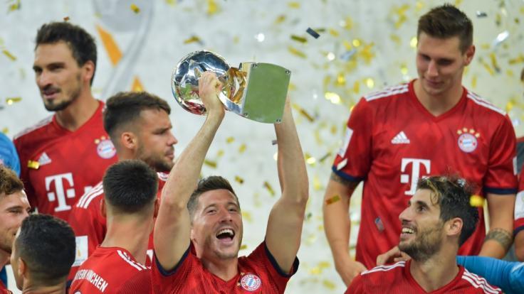 Bayerns Spieler um den zweifachen Torschützen Robert Lewandowski (M) freuen sich über den Sieg und den Gewinn des Supercups. (Foto)