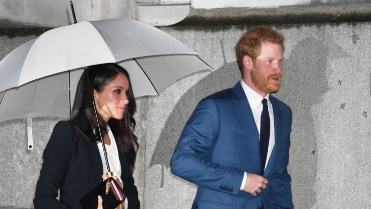 Meghan Markle und Prinz Harry bei ihrer Ankunft. Sie mit Schirm, er oben ohne. (Foto)