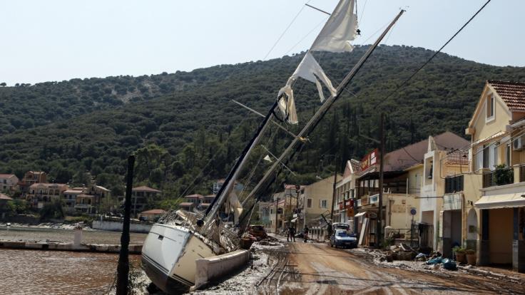 Griechenland, Kefalonia: Eine Segelyacht liegt nach einem Sturm neben einer Straße an Land.