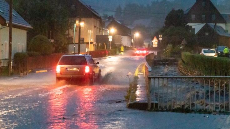 Wasser steht auf der Straße im Ortsteil Steinbach. Ein heftiges Unwetter war über der Stadt niedergegangen. (Foto)
