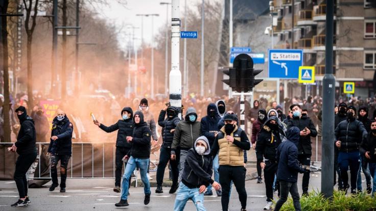 Demonstranten werfen auf einer Straße mit Steinen. (Foto)