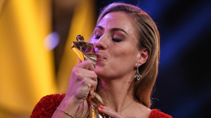 """Die Tennisspielerin Angelique Kerber steht bei der Verleihung der Trophäe zur """"Sportlerin des Jahres"""" auf der Bühne und küsst ihren Pokal. (Foto)"""