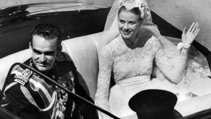 Fürst Rainier III. von Monaco und seine Braut, die US-amerikanische Filmschauspielerin Grace Kelly winken nach ihrer Hochzeit den Schaulustigen zu.
