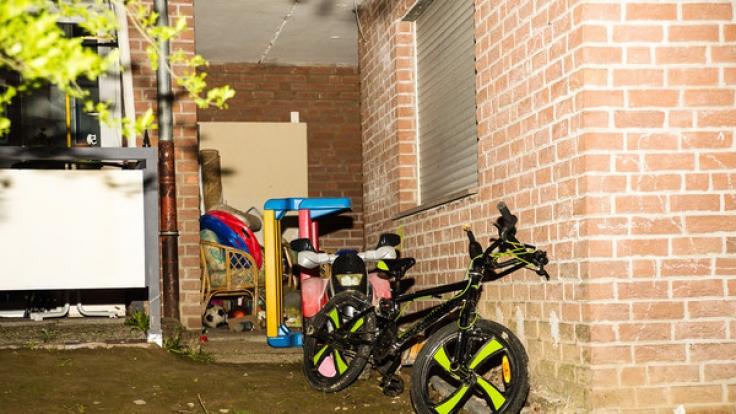 Im Hof des Wohnhauses sieht man das Fahrrad eines Kindes.