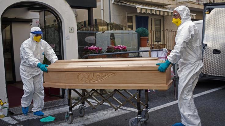Medizinisches Personal in Schutzanzügen trägt einen Sarg mit dem Leichnam einer 87-jährigen Frau aus einem Hotel. (Foto)