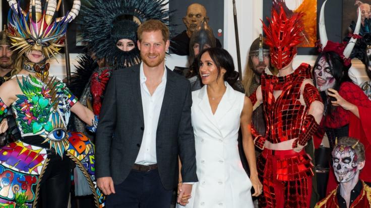 Inmitten der zu Halloween kostümierten Gestalten sehen Prinz Harry und seine schwangere Ehefrau Meghan Markle beinahe farblos aus.