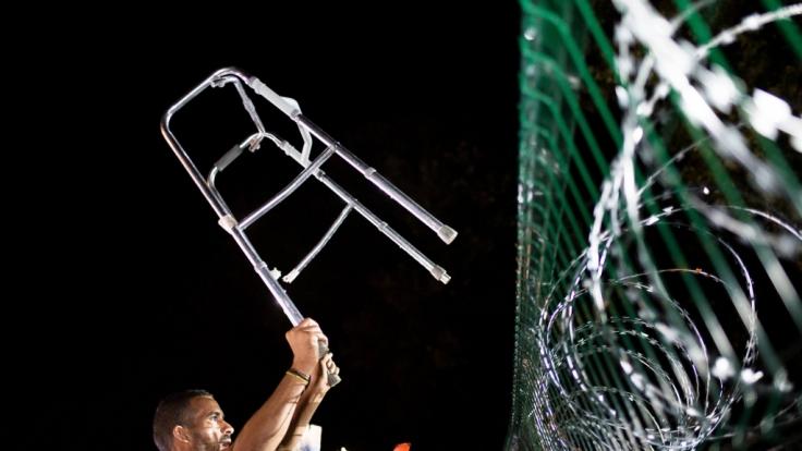 Ein Flüchtling an der serbisch-ungarischen Grenze. Um sich gegen den Ansturm zu schützen, hat Ungarn einen Zaun errichtet. Die Überquerung der Grenze ist seit kurzem gesetzeswidrig. (Foto)
