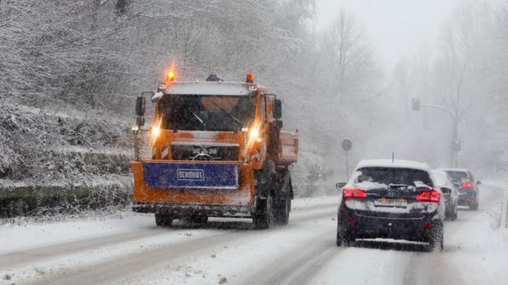 Ein Streufahrzeug befährt eine verschneite Strasse bei Aachen.