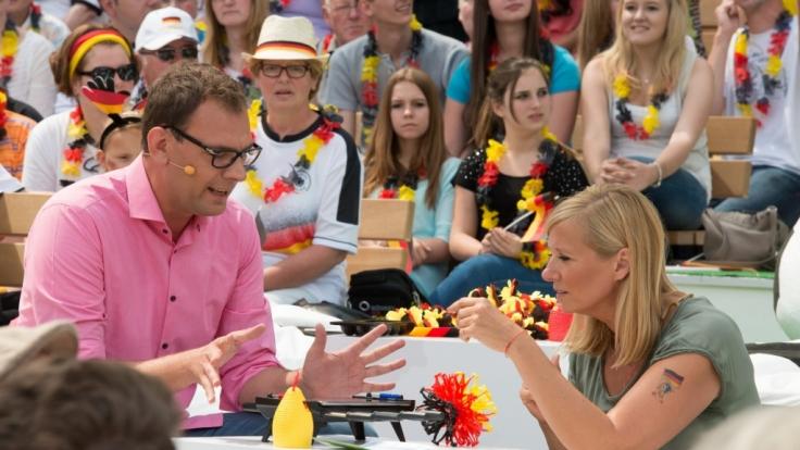 Martin Leutke und Andrea Kiewel testen WM-Gadgets.