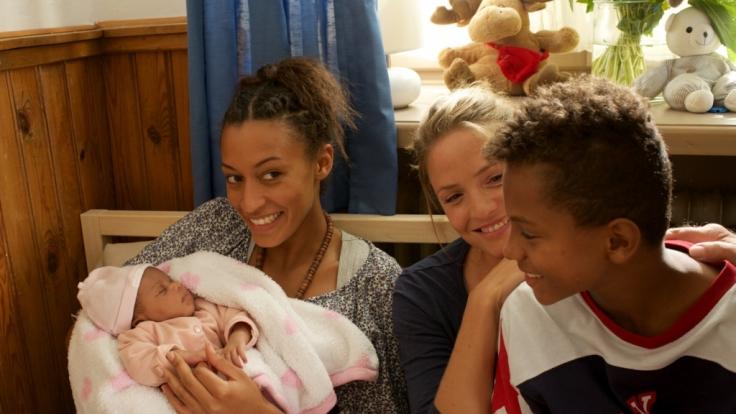 Hebamme Lena (Patricia Aulitzky, Mitte) zögert nicht lange und nimmt Senait (Sabrina Ceesay, links) und ihren Sohn Anbessa (Ruben Felipe, rechts) bei sich auf, die aus Eritrea geflüchtet sind.