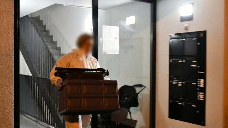 Eine Mitarbeiterin der Spurensicherung trägt einen Kasten aus einem Haus im Stadtteil Eberstadt. In einer Wohnung in Darmstadt waren Leichenteile gefunden worden. (Foto)