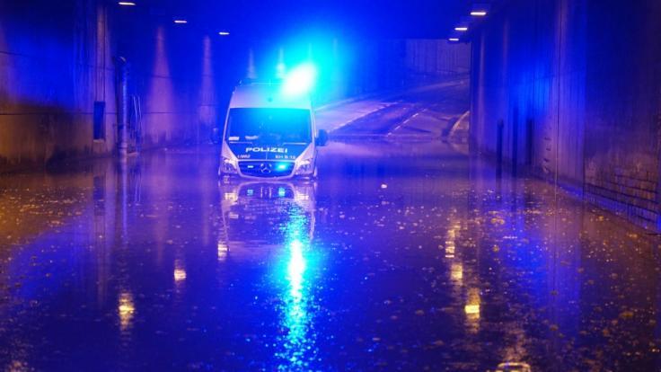 Ein Polizeifahrzeug blinkt noch mit Blaulicht, nachdem es in einer überschwemmten Unterführung in Stuttgart liegen geblieben ist. (Foto)