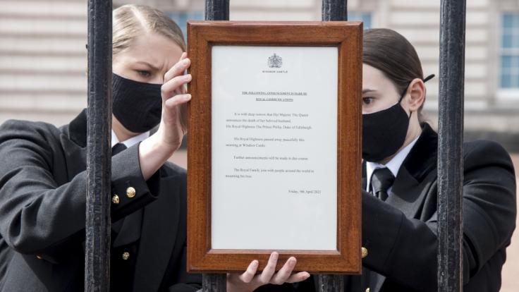 Eine Mitarbeiterin hängt eine Tafel mit der Todesmitteilung des britischen Prinz Philip an das Tor des Buckingham Palace. (Foto)