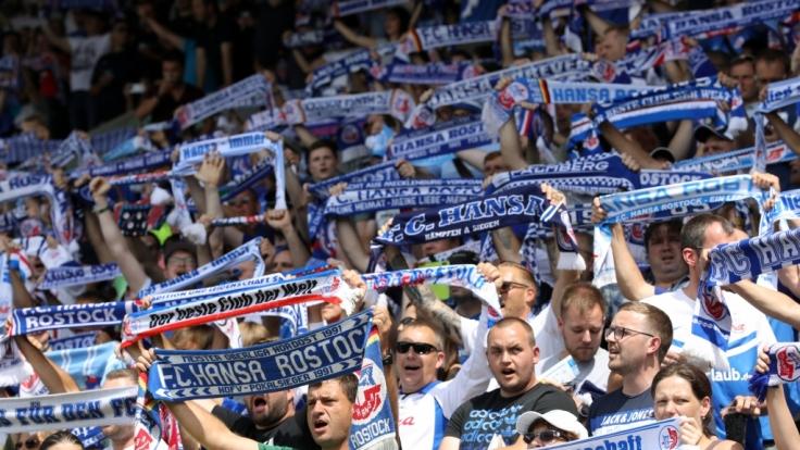 Die Fans heben ihre Schals zur Unterstützung der Spieler vom FC Hansa Rostock. (Symbolbild)
