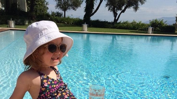 Pixie am Pool mit einer Sonnenbrille ihrer eigenen Kollektion und a-freiem Cocktail.