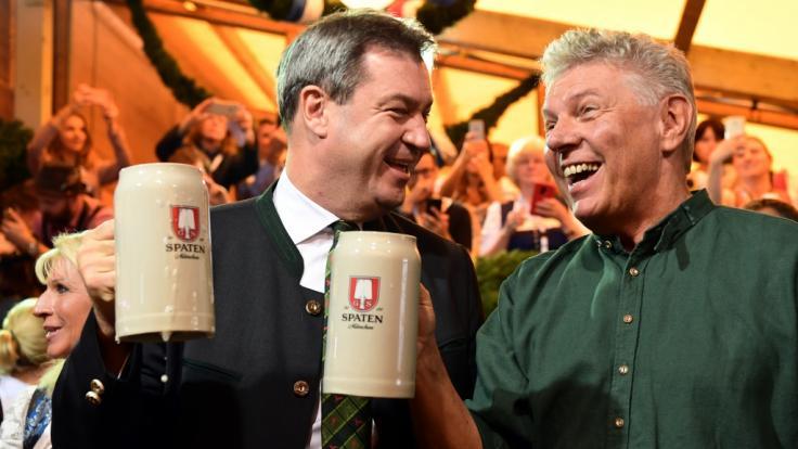 Markus Söder (l, CSU), Ministerpräsident von Bayern, und Dieter Reiter (SPD), Oberbürgermeister von München, stoßen mit zwei Maßkrügen nach dem traditionellen Fassanstich an. (Foto)