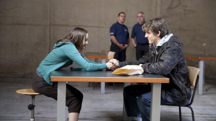 Jäckies (Oskar Bökelmann) besucht Simone (Lena Urzendowsky) in der Untersuchungshaft.