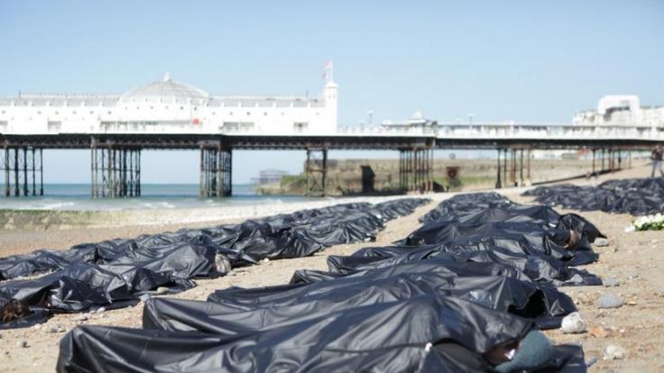 In schwarzen Leichensäcken zeigten sich die Aktivisten von Amnesty International am Strand von Brighton, um auf die hunderten verstorbenen Flüchtlinge aufmerksam zu machen.